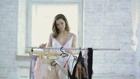 La mujer en el camisón blanco viene atormentar con las suspensiones para elegir la ropa interior metrajes