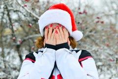 La mujer en el casquillo Santa Claus cubre su cara con sus manos Foto de archivo