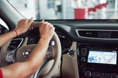 La mujer en el coche interior mantiene la rueda el dar vuelta alrededor en de pasajeros de mirada sonrientes taxista de la idea d Imágenes de archivo libres de regalías