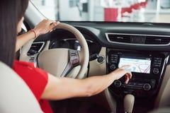 La mujer en el coche interior mantiene la rueda el dar vuelta alrededor en de pasajeros de mirada sonrientes taxista de la idea d Fotos de archivo libres de regalías