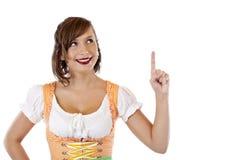 La mujer en el dirndl más oktoberfest señala hasta espacio del anuncio Imágenes de archivo libres de regalías