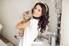 La mujer en el dormitorio con el gato en sus brazos Imágenes de archivo libres de regalías
