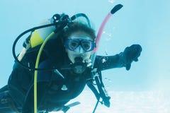 La mujer en el entrenamiento del equipo de submarinismo se sumergió en la piscina que mostraba los pulgares abajo Fotografía de archivo