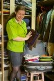 La mujer en el guardarropa pila de discos cosas en una maleta Fotos de archivo libres de regalías