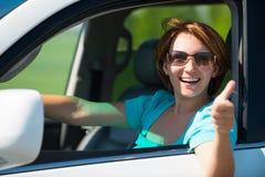 La mujer en el nuevo coche blanco en la naturaleza con los pulgares sube la muestra Imagen de archivo libre de regalías