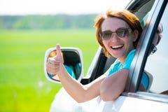 La mujer en el nuevo coche blanco en la naturaleza con los pulgares sube la muestra Foto de archivo libre de regalías