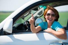 La mujer en el nuevo coche blanco en la naturaleza con los pulgares sube la muestra Fotos de archivo libres de regalías
