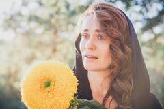 La mujer en el pañuelo en el parque, rasgones en sus ojos, sonriendo y sosteniéndose cerca de la cara de un girasol emociones imagen de archivo