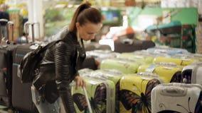 la mujer en el pasillo del supermercado elige una maleta para el viaje de las vacaciones almacen de video