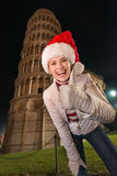 La mujer en el sombrero de Papá Noel que muestra los pulgares sube cerca de la torre inclinada de Pisa Imágenes de archivo libres de regalías