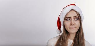 La mujer en el sombrero de Papá Noel separó de par en par las manos y la mirada de la cámara con la cara embarazosa Foto de archivo