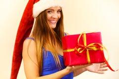La mujer en el sombrero de Papá Noel sostiene la caja de regalo Tiempo de la Navidad Imagenes de archivo