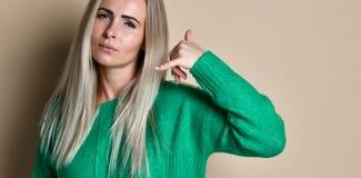 La mujer en el suéter verde que hace gesto del teléfono como dice: llámeme detrás con la mano y los fingeres como hablar en el te imágenes de archivo libres de regalías