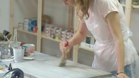 La mujer en el taller está trabajando en los tableros de madera, creando un efecto de la antigüedad metrajes