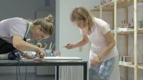 La mujer en el taller está trabajando en los tableros de madera, creando un efecto de la antigüedad almacen de video