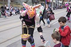 La mujer en el traje de Pascua distribuye los regalos a los niños a lo largo del este de la calle de la reina en el desfile 2017  Imagen de archivo libre de regalías