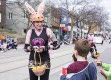La mujer en el traje de Pascua distribuye los regalos a los niños a lo largo del este de la calle de la reina en el desfile 2017  Fotografía de archivo libre de regalías