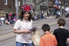 La mujer en el traje de Pascua distribuye los regalos a los niños a lo largo el este de la calle de la reina en el desfile 2017 d Fotografía de archivo libre de regalías