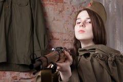La mujer en el uniforme militar ruso tira un rifle Soldado de sexo femenino durante la Segunda Guerra Mundial Fotografía de archivo libre de regalías