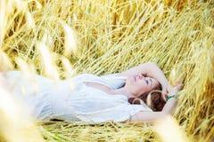 La mujer en el vestido blanco miente en un campo entre las espigas de trigo Fotografía de archivo