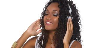 La mujer en equipo casual escucha la música con los auriculares - aislante Fotografía de archivo