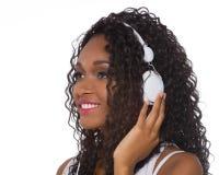 La mujer en equipo casual escucha la música con los auriculares - aislante Fotografía de archivo libre de regalías