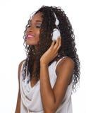 La mujer en equipo casual escucha la música con los auriculares - aislante Fotos de archivo libres de regalías