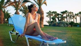 La mujer en gafas de sol se está sentando en una cubierta-silla entre las palmas metrajes