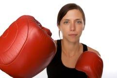 La mujer en gimnasia arropa, con los guantes de boxeo, fuerza Imagen de archivo libre de regalías