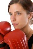 La mujer en gimnasia arropa, con los guantes de boxeo, fuerza Imagenes de archivo
