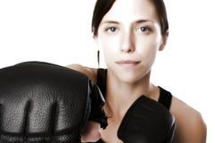 La mujer en gimnasia arropa, con los guantes de boxeo, fuerza Imágenes de archivo libres de regalías
