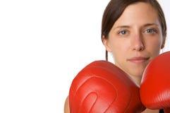 La mujer en gimnasia arropa, con los guantes de boxeo, fuerza Foto de archivo