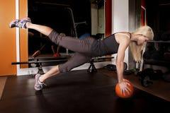 La mujer en gimnasio empuja hacia arriba la pierna encima de la bola Fotos de archivo