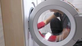 La mujer en guantes de goma rojos está lavando una lavadora con la esponja almacen de metraje de vídeo