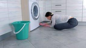 La mujer en guantes de goma rosados lava los muebles de la cocina con el paño El sentarse en el piso Vista lateral metrajes