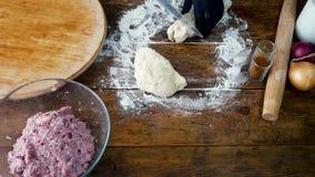 La mujer en guantes negros está cortando la pasta para cocinar la empanada con la carne almacen de metraje de vídeo