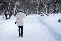 La mujer está saliendo en parque del invierno Imagen de archivo libre de regalías