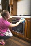 La mujer en la cocina que limpia el paño en el horno Foto de archivo libre de regalías