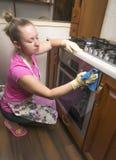 La mujer en la cocina que limpia el paño en el horno Imágenes de archivo libres de regalías