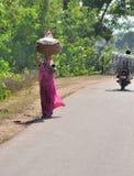 La mujer en la India lleva la cesta en su cabeza Imágenes de archivo libres de regalías