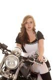 La mujer en la motocicleta sienta las piernas para echar a un lado el negro blanco Imagen de archivo