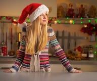 La mujer en la Navidad adornó la cocina que miraba en el co Fotografía de archivo libre de regalías