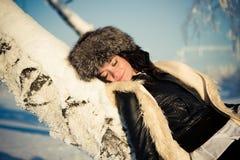 La mujer en la nieve se inclinaba en un árbol Imagenes de archivo