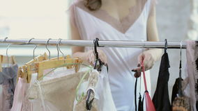 La mujer en la ropa blanca viene atormentar con las suspensiones para elegir la ropa almacen de video
