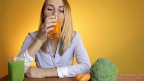 La mujer en la tabla al lado de los jugos y de las verduras almacen de metraje de vídeo