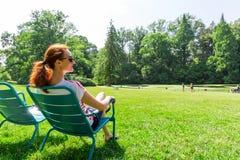 La mujer en lentes se relaja en pradera Foto de archivo