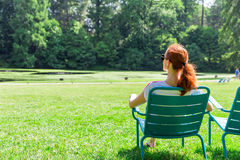 La mujer en lentes se relaja en pradera imagen de archivo