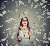 La mujer en los vidrios que bombean los puños celebra éxito debajo de la lluvia del dinero Fotos de archivo libres de regalías