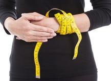 La mujer en negro con la cinta métrica amarilla en su mano, healt Imagen de archivo