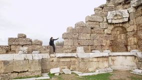 La mujer en negro se sienta en piedra vieja de la pared y hace el selfie almacen de metraje de vídeo